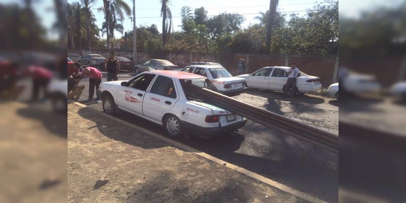Tubos de acero caen de camioneta y atraviesan un taxi