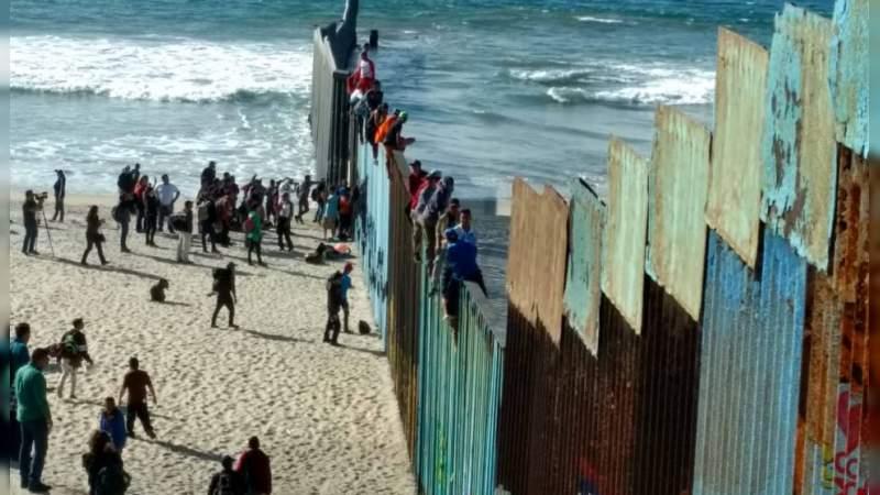 Migrantes centroamericanos trepan muro fronterizo en Tijuana